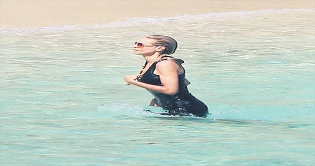 Elbise ve gözlükle denize girdi